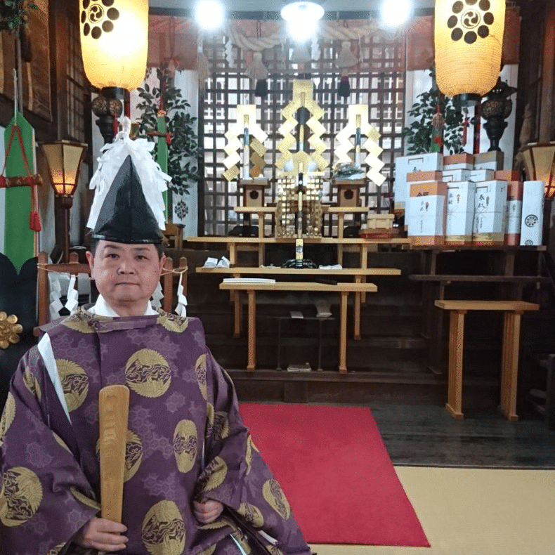 A Shinto priest in front of a Shinto shrine